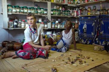 "TO GO WITH AFP STORY BY SUSAN NJANJI (FILES) This file photo taken on November 14, 2015 shows twelve-year-old South African Kyle Todd (L) performing a divination by looking at bones and objects during his initiation ceremony to become a Sangoma or traditional healer at a traditional healer school in Pretoria, South Africa. Kyle officiates as ""sangoma"", a medium and traditional healer in South Africa which is extremely rare for a white man in this country. South African traditional healers are practitioners of traditional African medicine in Southern Africa. They fulfill different social and political roles in the community, including divination, healing physical, emotional and spiritual illnesses, directing birth or death rituals, finding lost cattle, protecting warriors, counteracting witches, and narrating the history, cosmology, and myths of their tradition. / AFP / MUJAHID SAFODIEN"